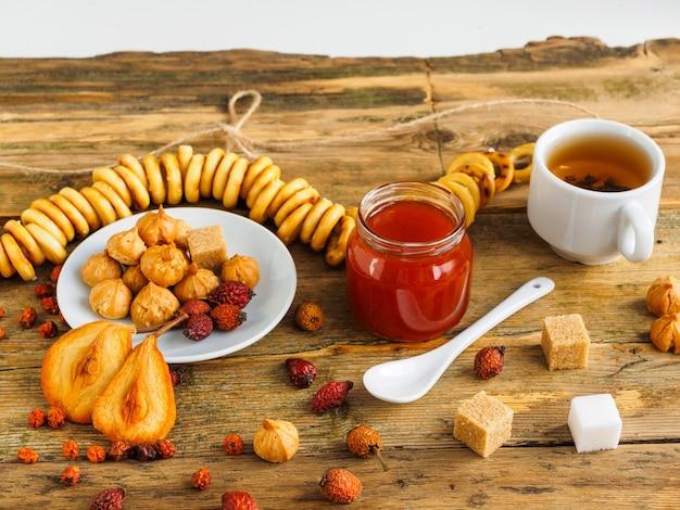 Filiżanka herbaty, dżemu, bułeczki i słodycze na drewnianym stole.