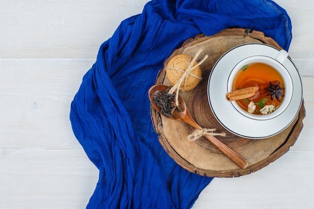 Filiżanka herbaty, goździki i ciasteczka na desce z niebieskim szalikiem