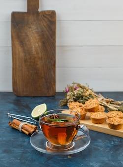 Filiżanka herbaty i ciasteczek z ciasteczkami, kwiatami, cynamonem, limonką i sitkiem do herbaty