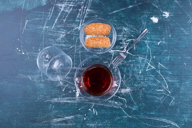 Filiżanka herbaty i ciasteczka na szarej powierzchni