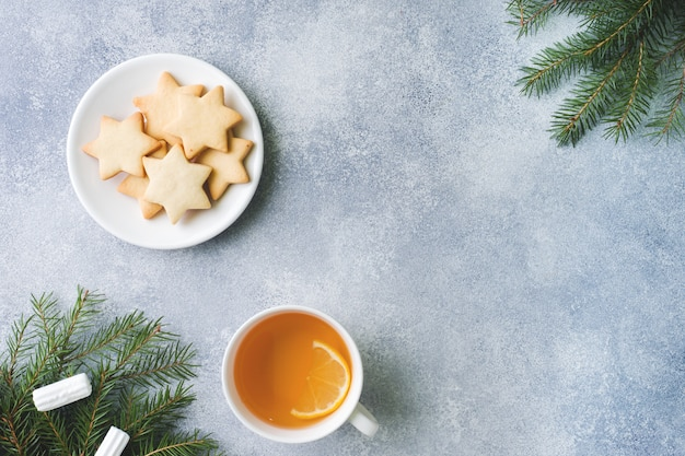 Filiżanka herbaty i ciastek, gałązki sosny, laski cynamonu, gwiazdki anyżu