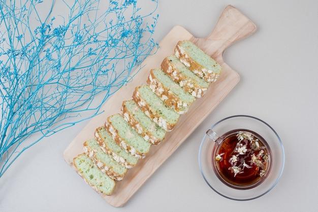 Filiżanka herbaty i ciasto plastry na białym z niebieską rośliną.
