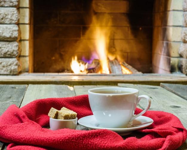Filiżanka herbaty i cukru, rzeczy wełny w pobliżu przytulny kominek, dom, wakacje zimowe, poziome.