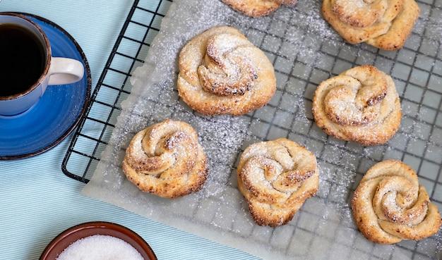 Filiżanka herbaty i domowy twarożek kruche ciasteczka w kształcie róż jasne tło widok z góry
