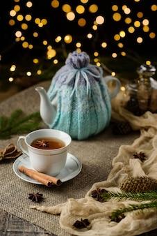 Filiżanka herbaty i imbryk na stole z laskami cynamonu, anyż