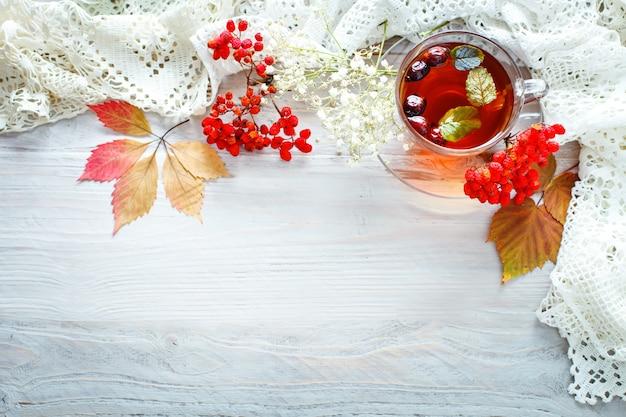 Filiżanka herbaty i jagód jarzębiny na drewnianym stole. jesienna martwa natura.
