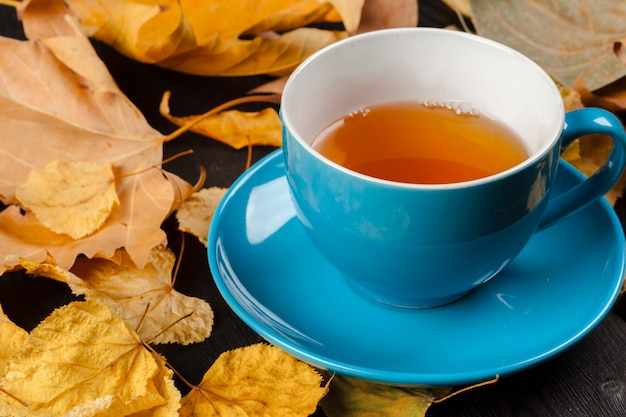 Filiżanka herbaty i jesień liście na stole