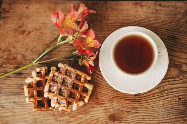 Filiżanka herbaty i kwiatów. alstroemeria i filiżanka herbaty. wiedeńskie gofry na drewnianym tle. poranne śniadanie. piękna martwa natura