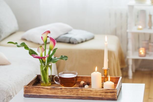 Filiżanka herbaty i kwiatów na drewnianej tacy w pomieszczeniu