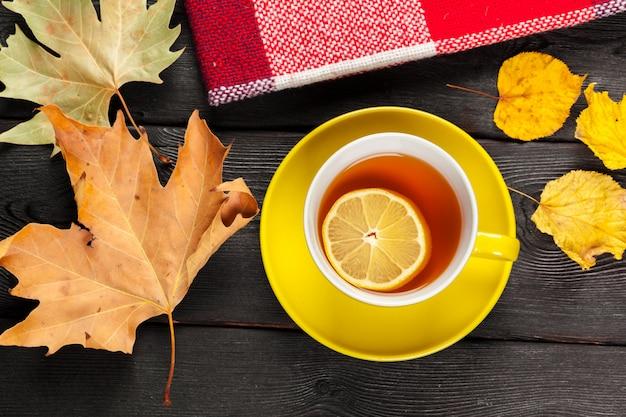Filiżanka herbaty i liści jesienią na stole