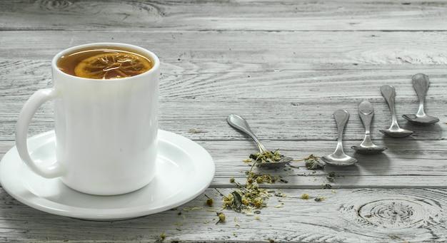 Filiżanka herbaty i łyżki na pięknym białym drewnianym stole, zima, jesień