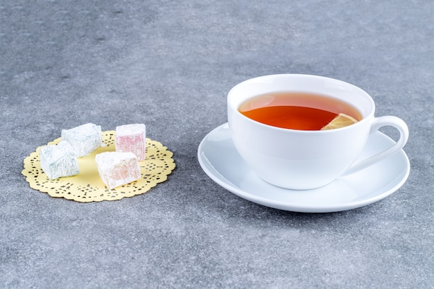 Filiżanka herbaty i miękkie cukierki na marmurowej powierzchni