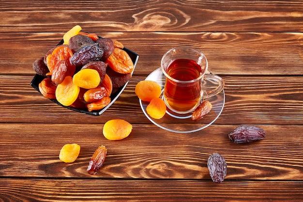 Filiżanka herbaty i mieszanka suszonych owoców w talerzu na drewnianym stole