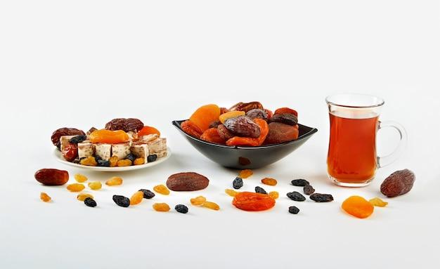 Filiżanka herbaty i mieszanki suszonych owoców w talerzu na białym tle