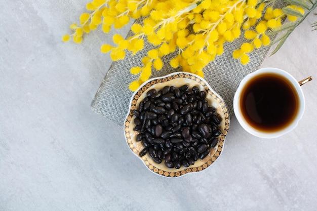 Filiżanka herbaty i miska cukierków z kwiatami. zdjęcie wysokiej jakości