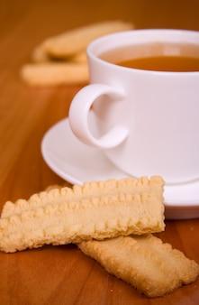 Filiżanka herbaty i niektóre ciastka na drewnianym stole