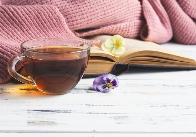Filiżanka herbaty i otwarta książka na lekkim drewnianym stole. koncepcja czytania. bezpłatne miejsce na kopię.