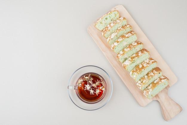 Filiżanka herbaty i plastry ciasta pistacjowego na białej powierzchni