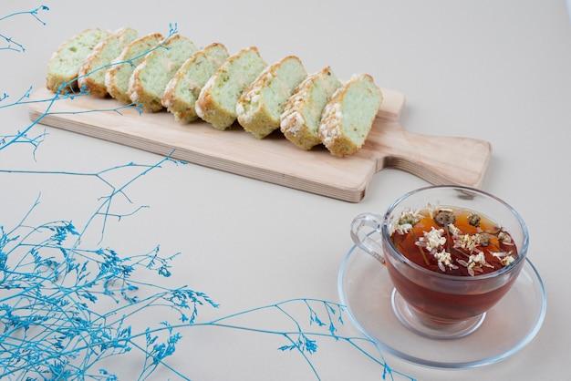 Filiżanka herbaty i plastry ciasta pistacjowego na białym tle.