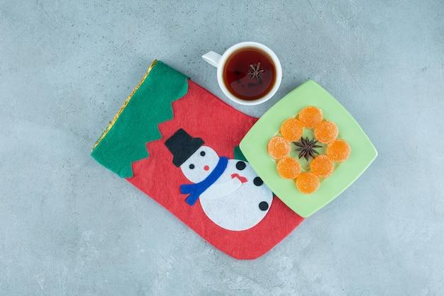 Filiżanka herbaty i półmisek marmolady na świątecznej skarpetce na marmurze.