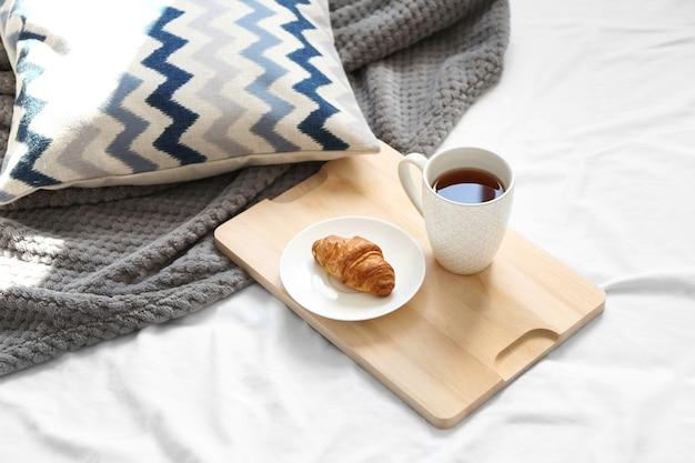 Filiżanka herbaty i rogalika na drewnianej tacy. śniadanie w łóżku