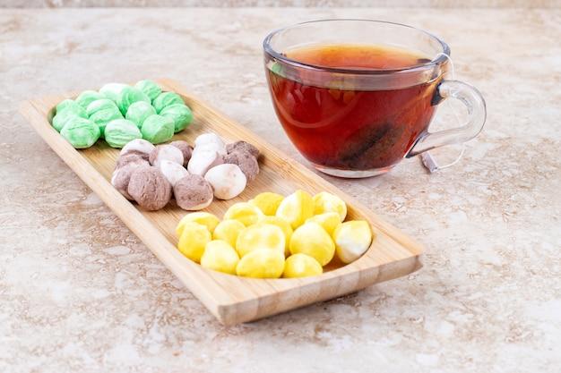 Filiżanka herbaty i różne cukierki w małej drewnianej tacy