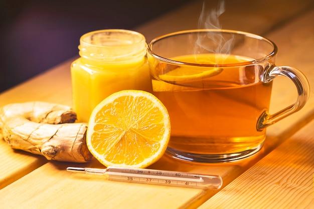 Filiżanka herbaty i słoik miodu na drewnianym stole