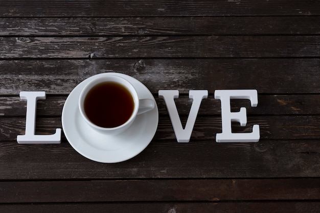 Filiżanka herbaty i słowo miłości z białych drewnianych liter