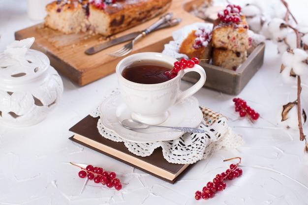 Filiżanka herbaty i spodek, babeczka z czerwoną porzeczką na desce i białym tle, bawełniane kwiaty