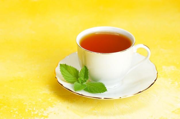 Filiżanka herbaty i spodek z liściem mięty