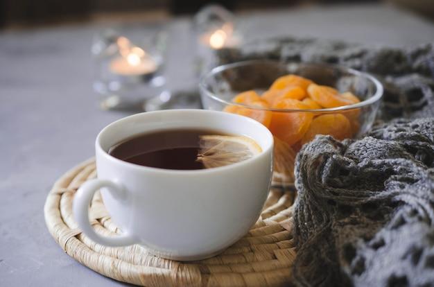 Filiżanka herbaty i suszonych moreli na stole, świece i dzianiny koc.
