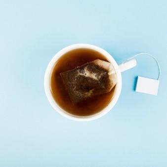 Filiżanka herbaty i torebki z herbatą