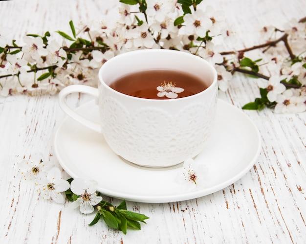 Filiżanka herbaty i wiosenny kwiat