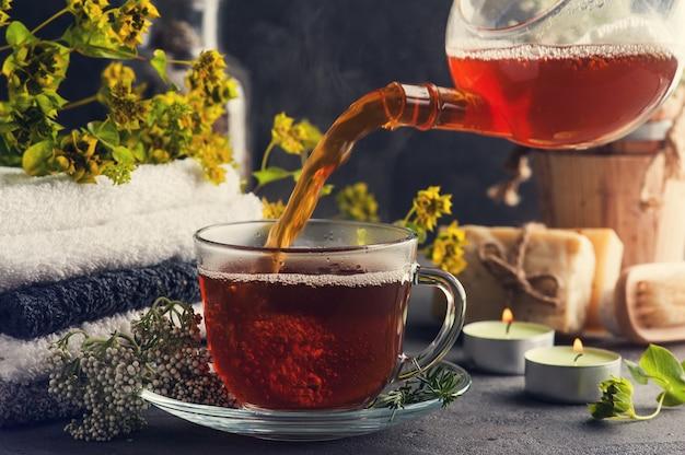 Filiżanka herbaty i zapalone świece w układzie spa