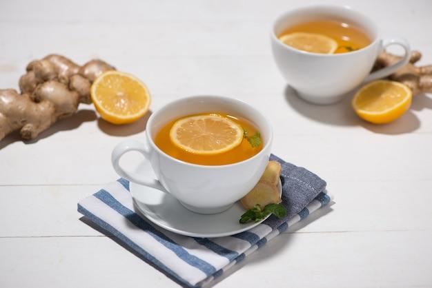 Filiżanka herbaty imbirowej z cytryną i miodem na białym tle drewnianych.