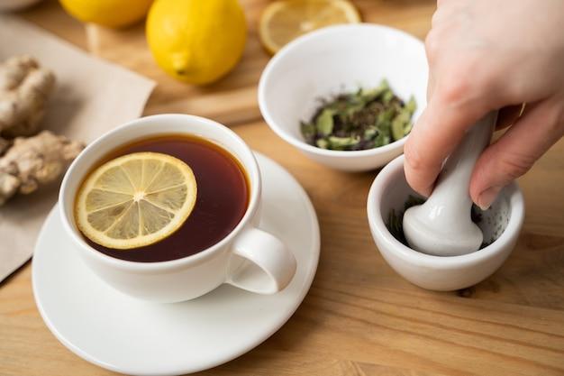 Filiżanka herbaty imbirowej z miodem i cytryną na drewnianym stole