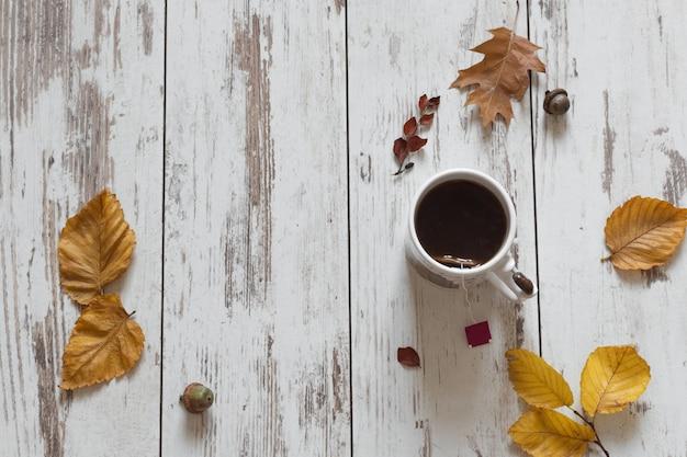 Filiżanka herbaty, jesień liście na drewnianym stołowym odgórnym widoku.