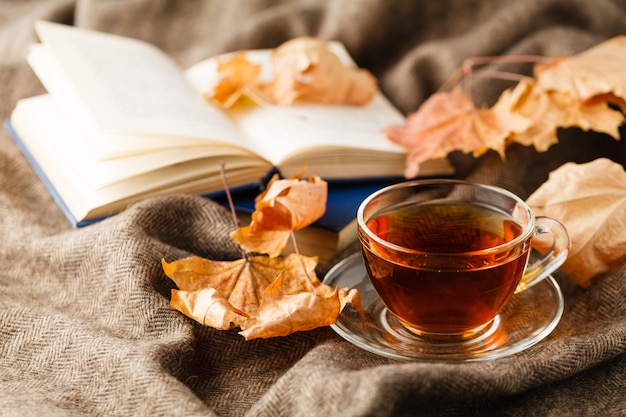 Filiżanka herbaty jesienią z opadającymi liśćmi obok