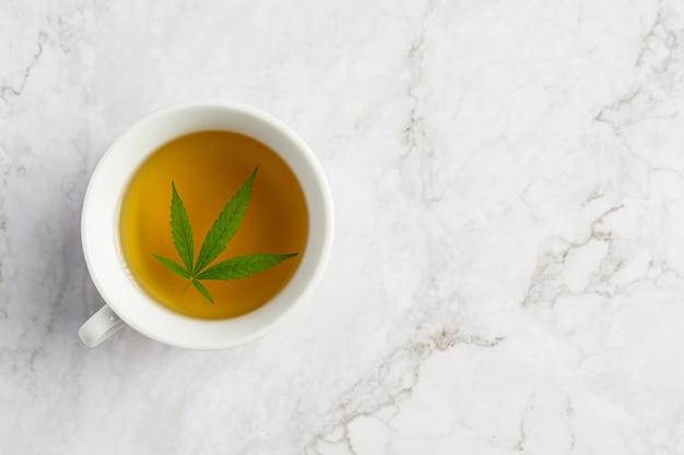 Filiżanka herbaty konopnej z liśćmi konopi położona na białej marmurowej podłodze
