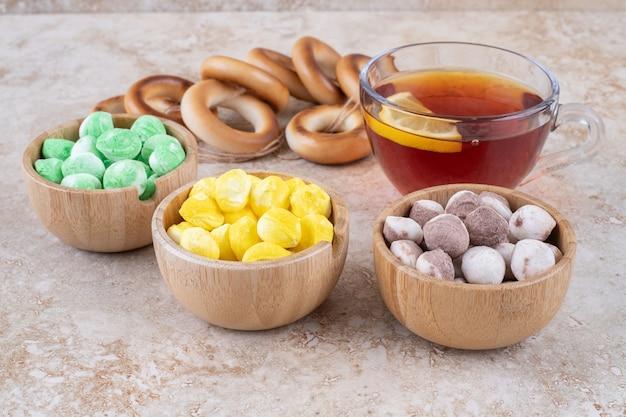 Filiżanka herbaty, krakersy i miski słodyczy na marmurowej powierzchni