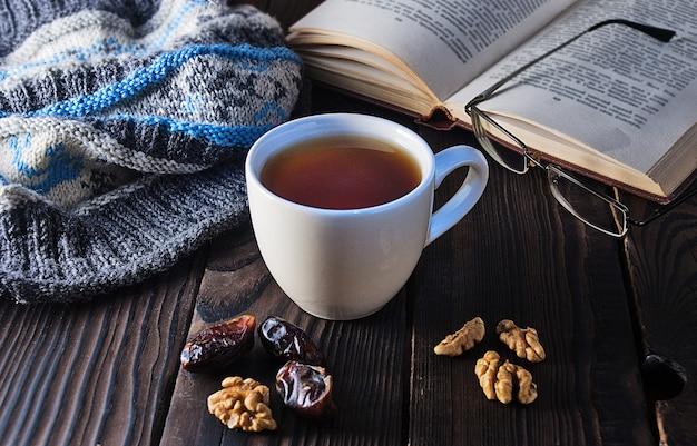 Filiżanka herbaty, książka i czapka z dzianiny na drewnianym stole