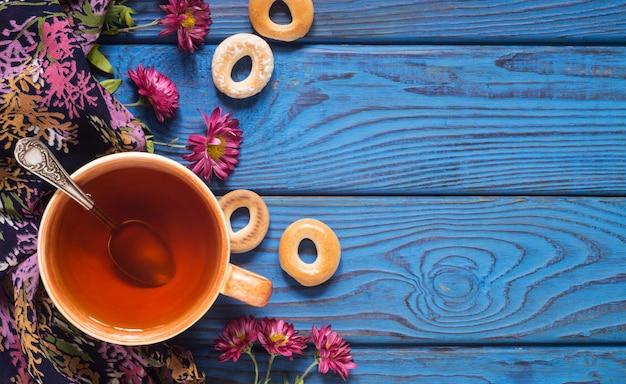 Filiżanka herbaty, kwiatów i bajgli na tle niebieskiego drewnianego stołu