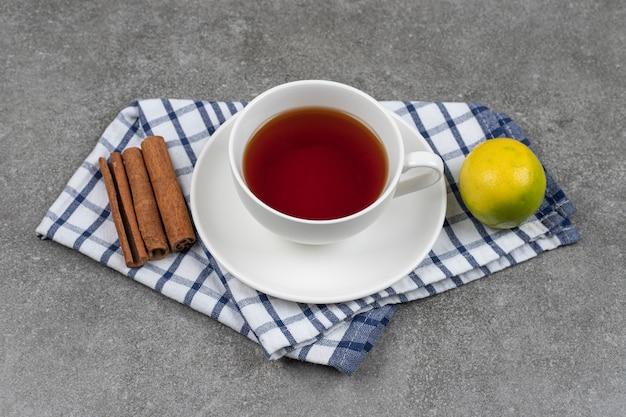 Filiżanka herbaty, laski cynamonu i cytryna na marmurowej powierzchni