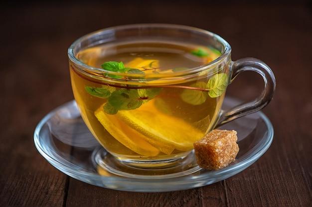 Filiżanka herbaty lemon z plasterkami cytryny, cukrem trzcinowym i miętą na ciemnym drewnie.
