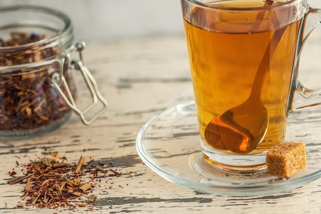 Filiżanka herbaty lipowej z cukrem trzcinowym na szarym drewnie.