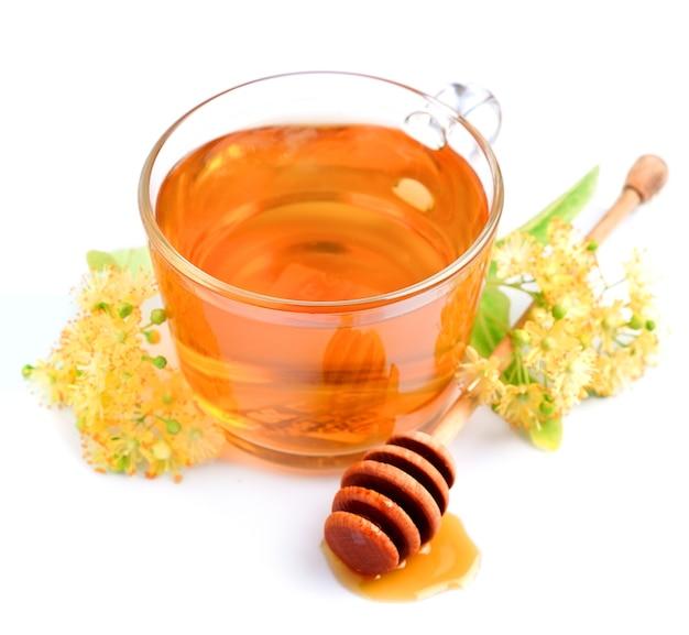 Filiżanka herbaty lipowej z kwiatami i miodem na białym tle