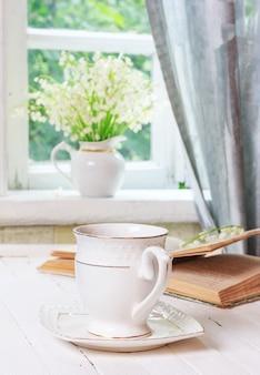 Filiżanka herbaty lub kawy i książka na białym drewnianym antycznym stole w stylu retro oraz bukiet kwiatów konwalii na parapecie w pobliżu otwartego okna w wiejskim domu w wiosenny poranek