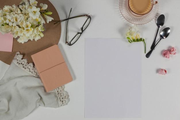 Filiżanka herbaty, łyżki, okulary, pamiętnik, ściereczka, pusta strona, papierowe kulki i kwiaty