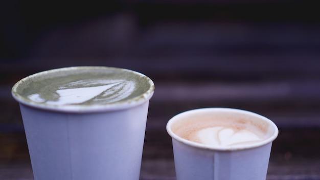 Filiżanka herbaty matcha z latte art i cappuccino w papierowym kubku na drewniane tła. niewyraźne tło.