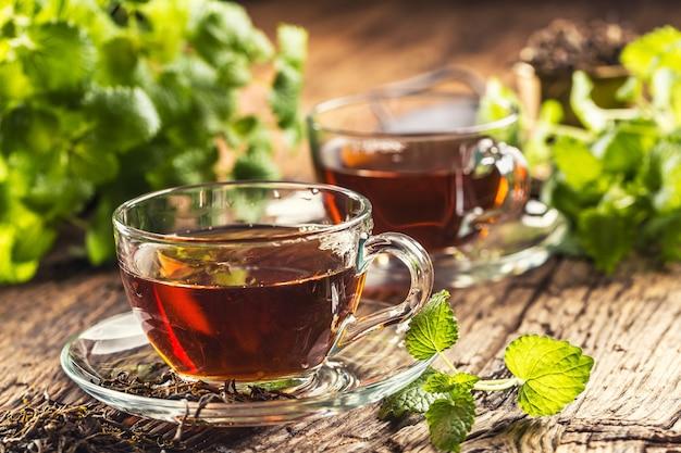 Filiżanka herbaty melisy z ziołami na drewnianym stole.